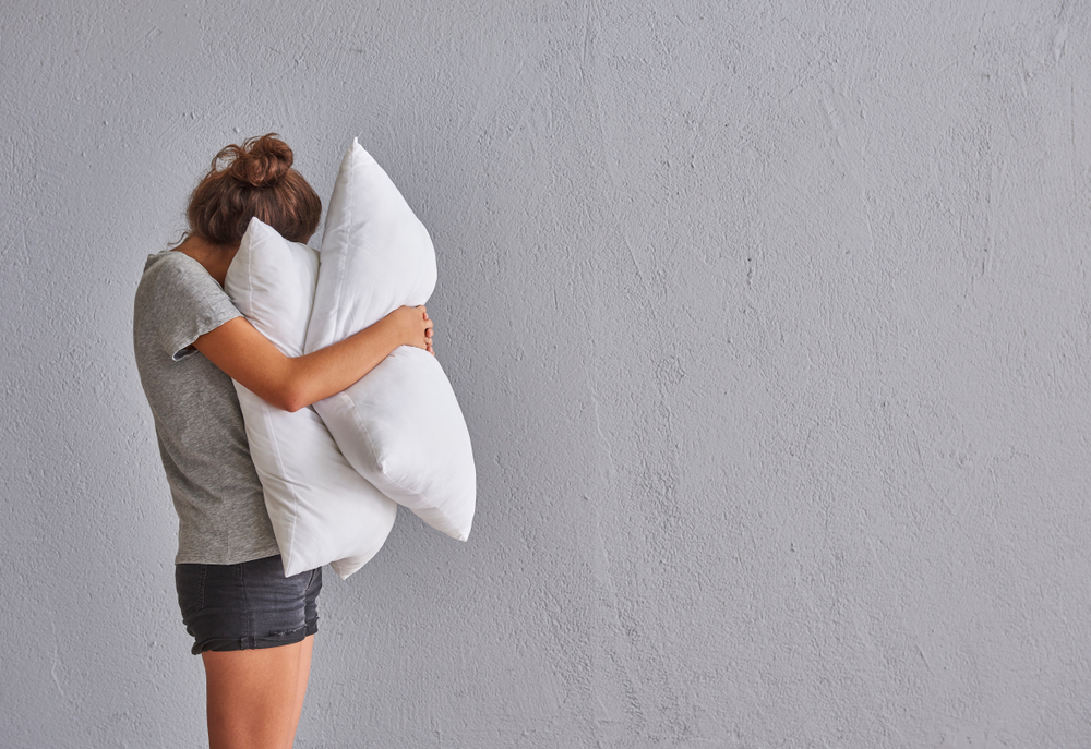 woman hugs two pillows